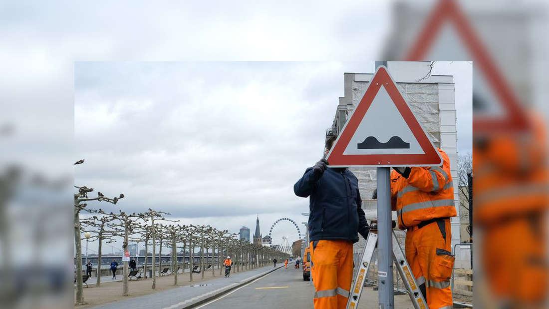 Bauarbeiter montieren ein Warnschild am Mannesmannufer