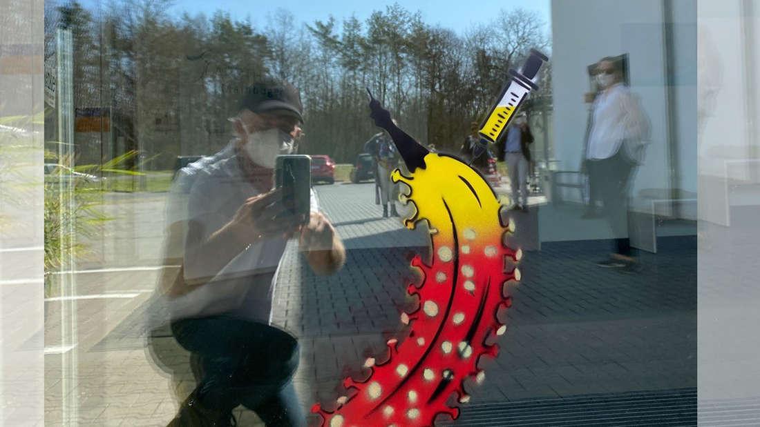 """Thomas Baumgärtel sprüht eine """"Impfbanane"""" an den Eingangsbereich eines Krankenhauses"""