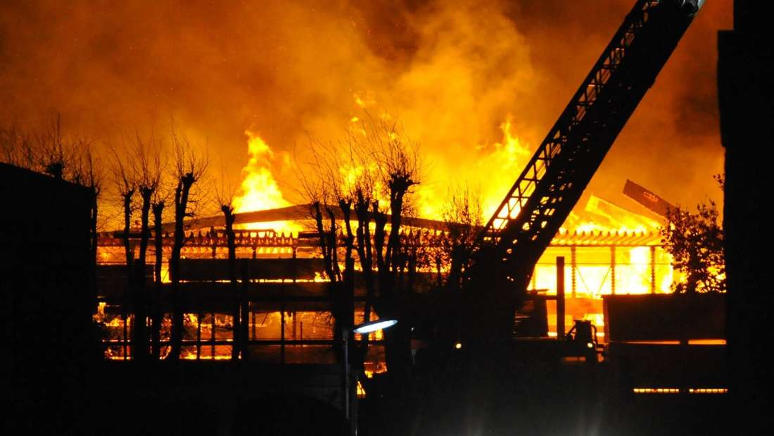 Ein Feuerwehrfahrzeug mit Drehleiter steht vor dem brennenden Gebäude eines Holzhandels in Viersen.