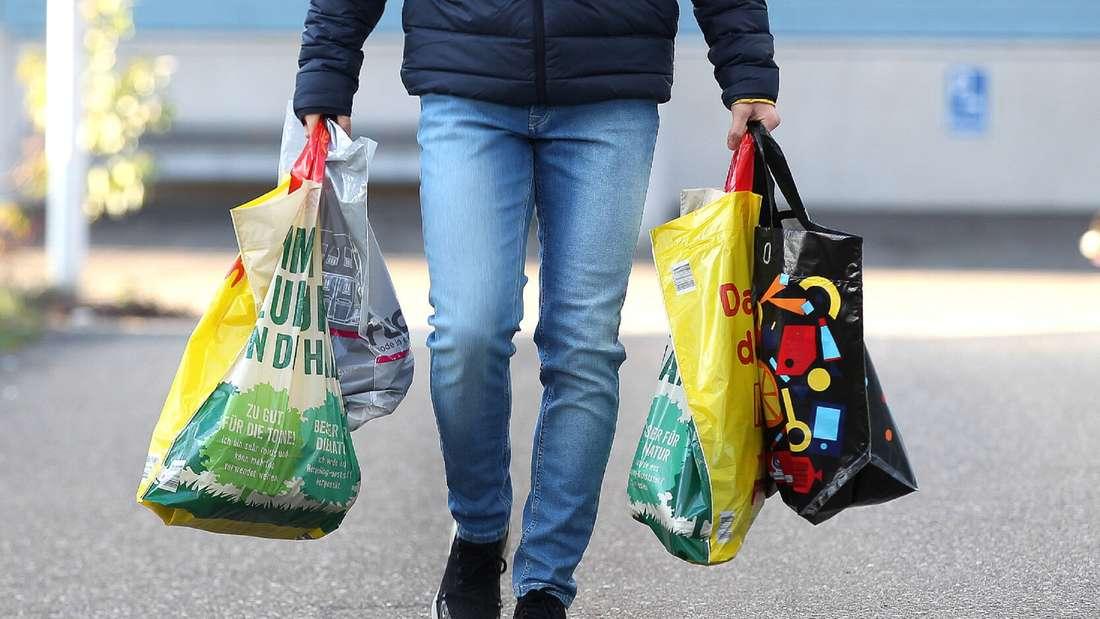 Ein Mann trägt mehrere Plastiktüten.