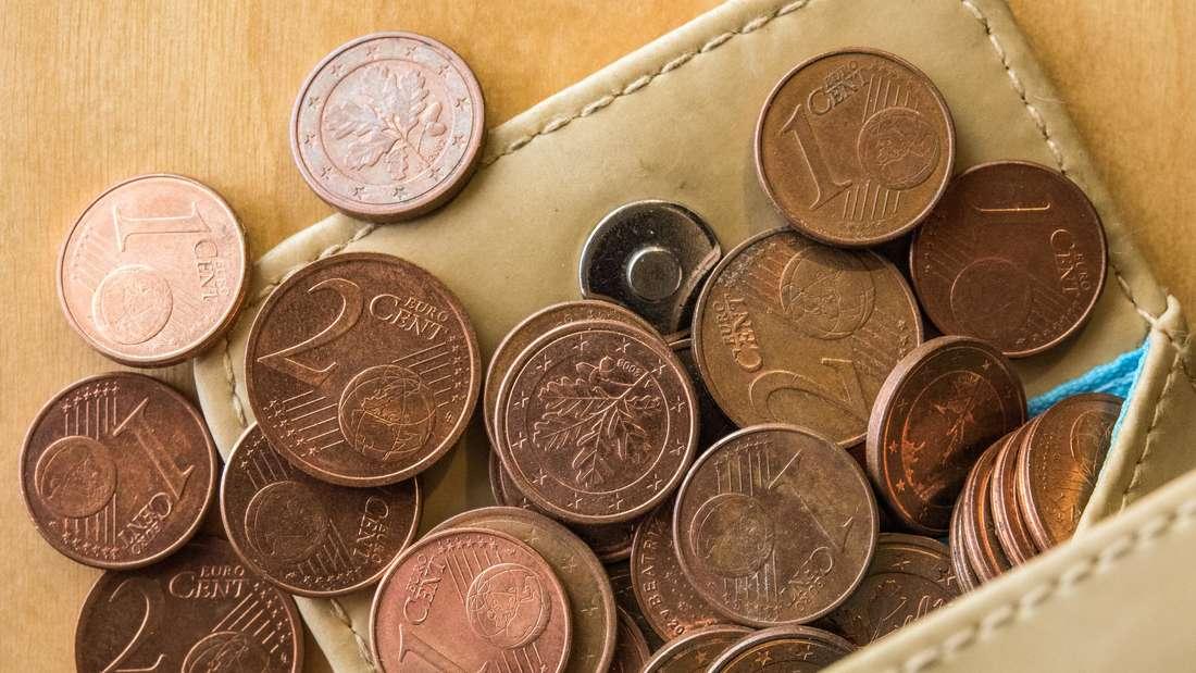 Kleingeld fällt aus einem Portemonnaie.