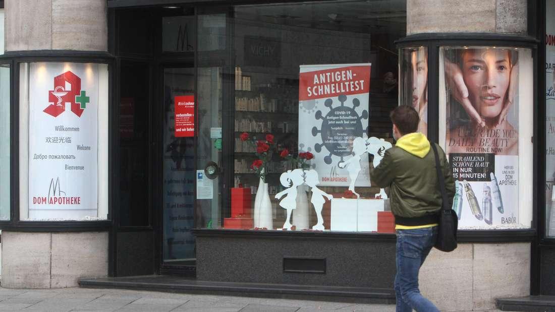 Eine Apotheke in Köln bietet Corona-Schnelltest auf einem Plakat im Schaufenster an.