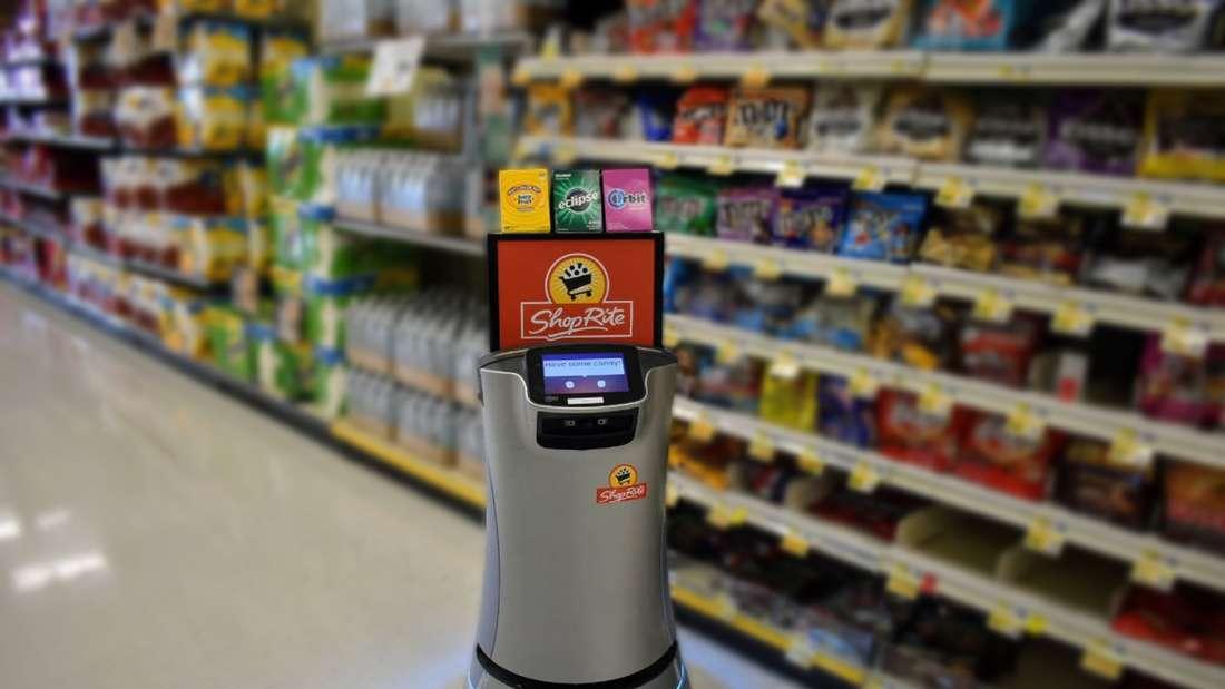 Der Roboter Smiley ist gepackt mit Schokoriegel und Kaugummis vom Hersteller Mars und fährt durch einen Supermarkt-Gang.