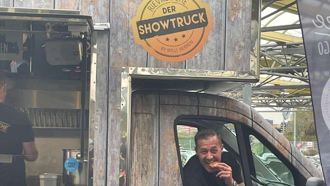 Willi Herren sitzt in seinem Foodtruck und beißt in einen Reibekuchen.