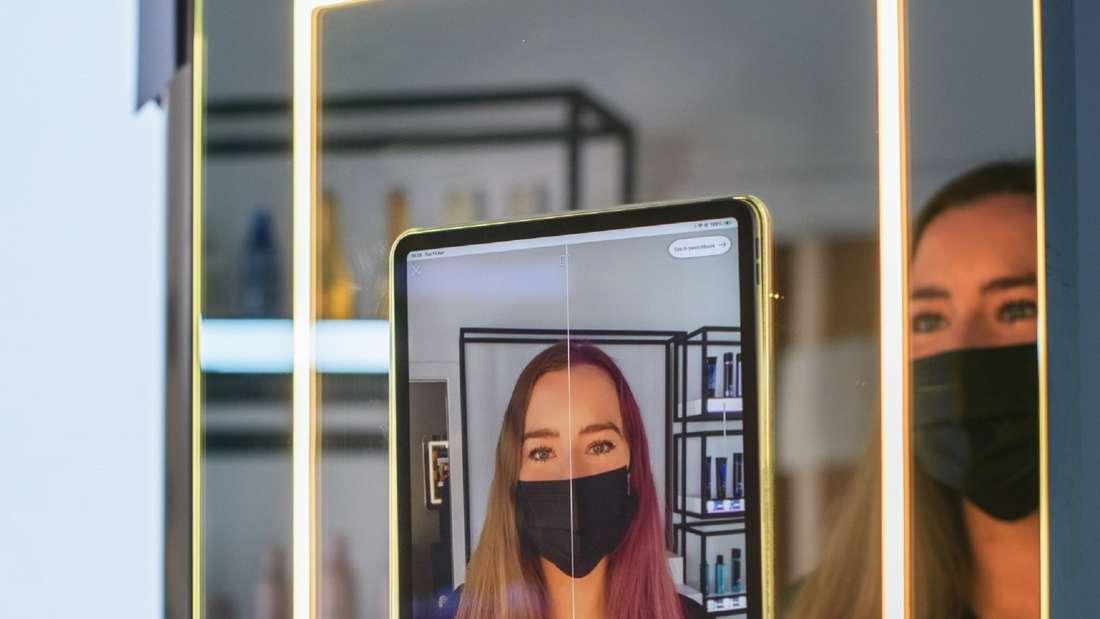 Eine Frau sitzt vor einem Spiegel und in einem Tablet erscheint ihr Spiegelbild inklusive Farbverändeurngen der Haarfarbe.