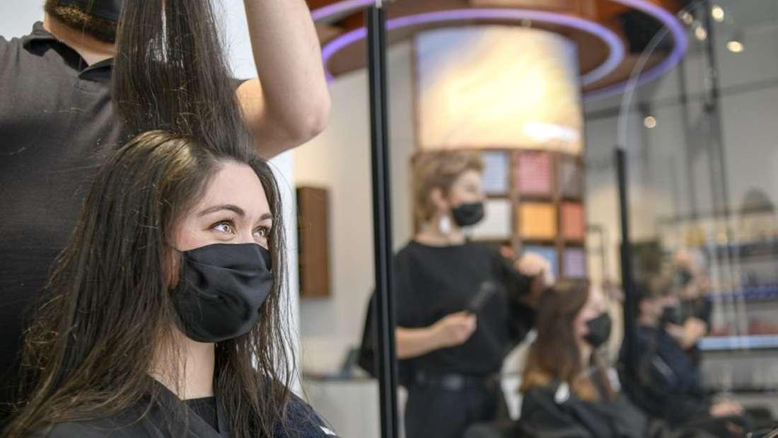 Eine Frau sitzt auf einem Stuhl in einem Friseursalon und bekommt die Harre gemacht.