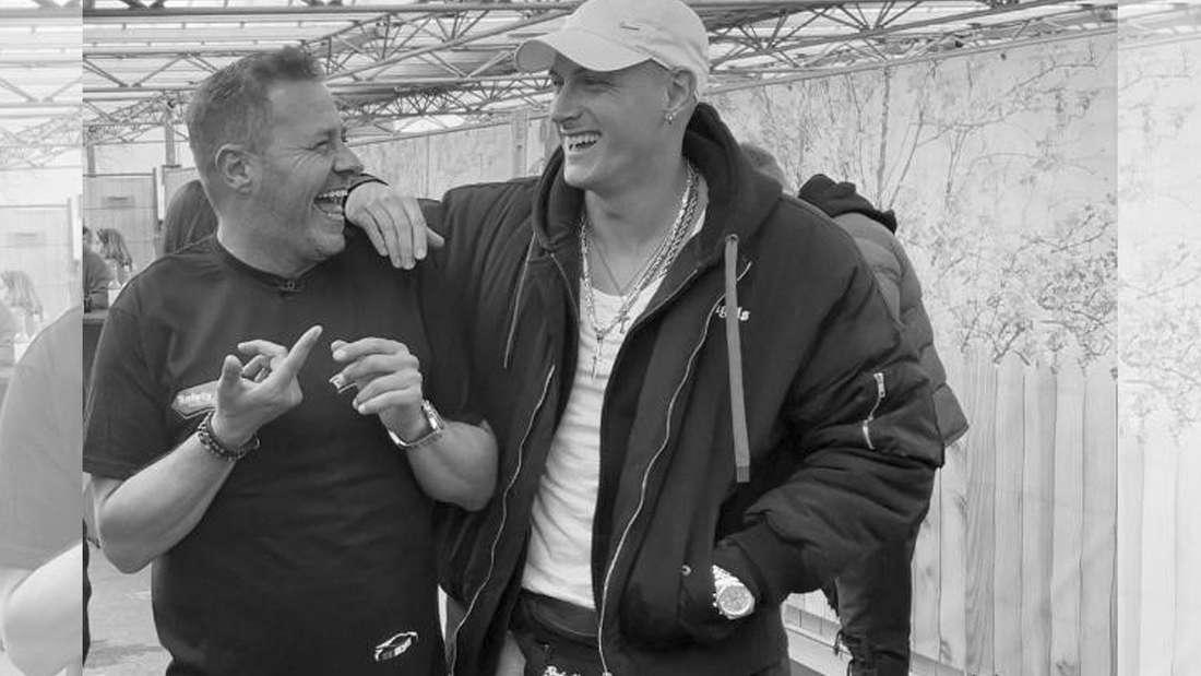 Calvin Kleinen legt Willi Herren den Arm auf die Schulter, beide lachen.
