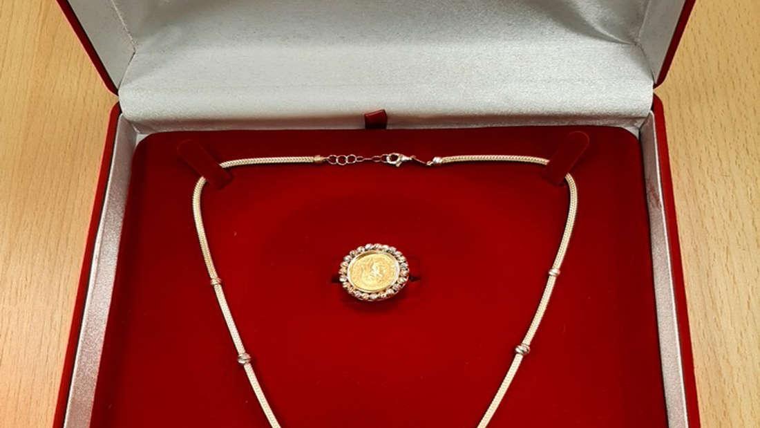 Eine goldene Halskette, ein Armband und ein Ring liegen in einem Schmuckkästchen.