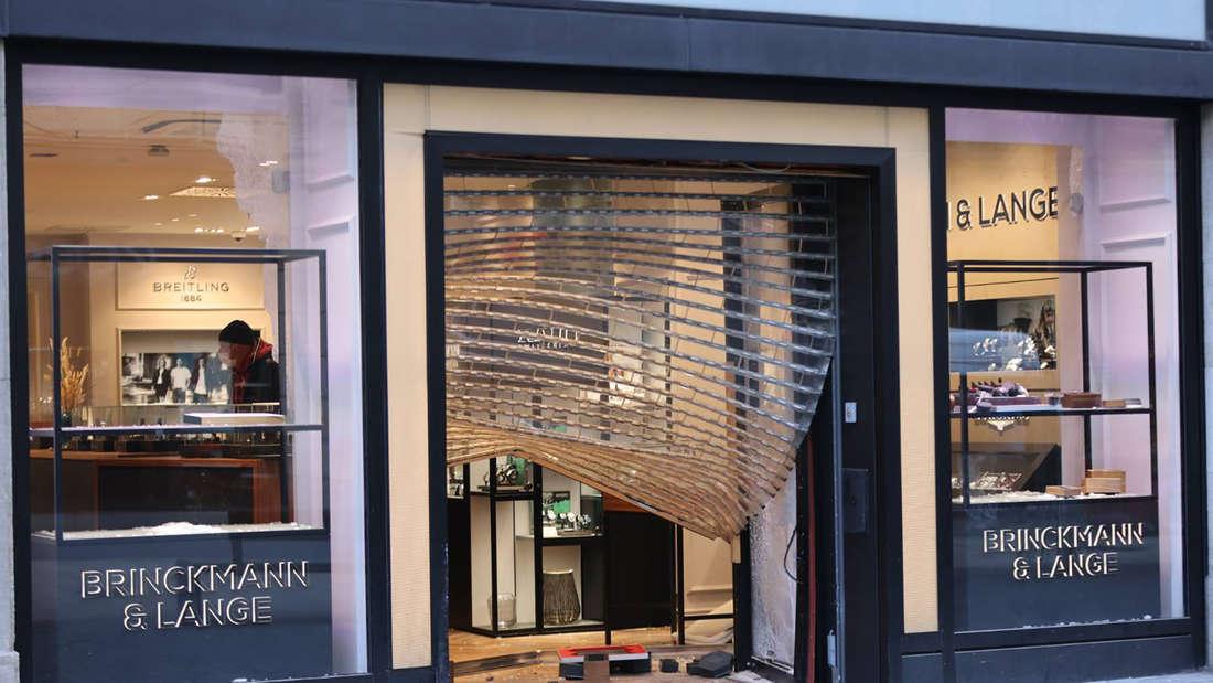 Das eingedrückte Rollgitter hängt am Eingang eines Juwelierladens herunter. Diebe haben einen spektakulären Einbruch bei einem Leipziger Juwelier verübt.