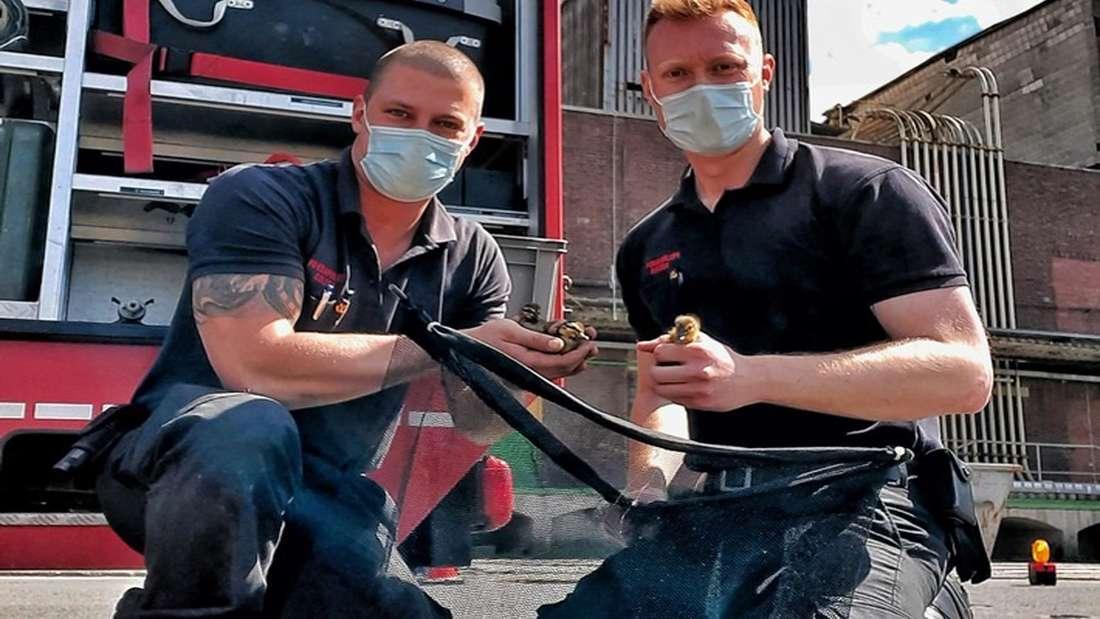 Zwei Feuerwehrleute halten zwei Entenküken in den Händen.