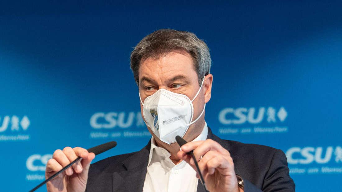 Markus Söder (CSU), Parteivorsitzender und Ministerpräsident von Bayern, richtet auf einer Pressekonferenz in der CSU-Parteizentrale seine Mikrofone am Pult aus.
