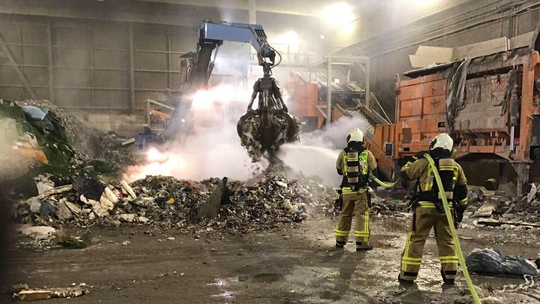 In einer Bottroper Lagerhalle wird brennender Gewerbemüll gelöscht.