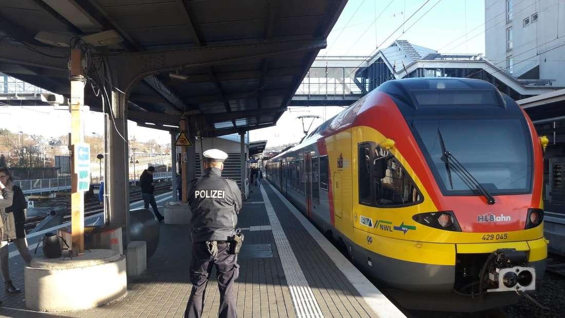 Ein Polizist steht am Hauptbahnhof Siegen neben einem einfahrenden Zug am Bahnsteig, Polizist von hinten zu sehen