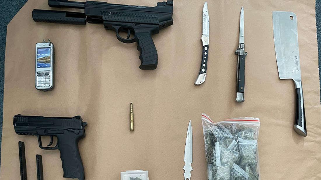 Waffen und Drogen liegen auf einem Tisch.
