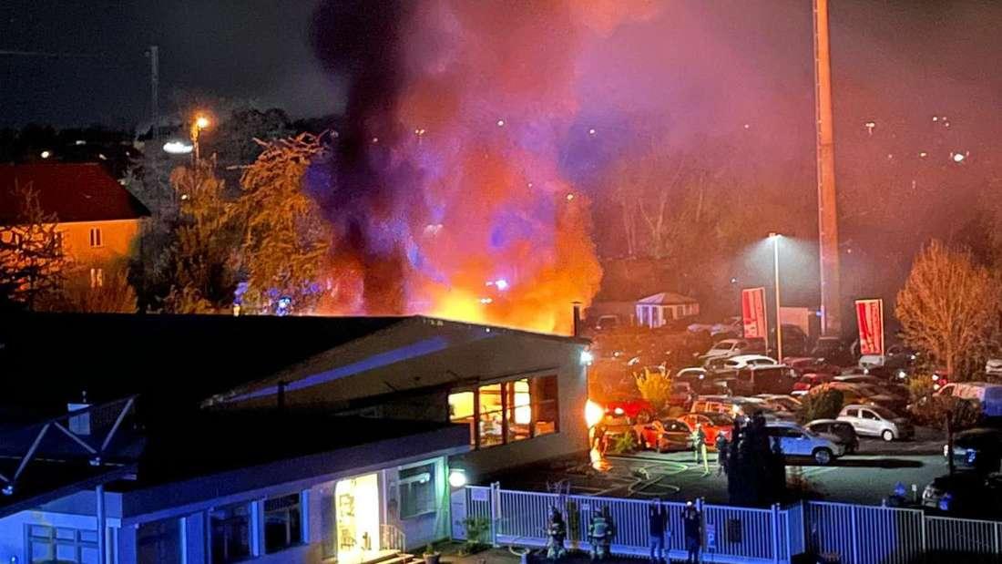 Einsatzkräfte der Feuerwehr löschen einen Brand auf dem Gelände eines Autohändlers in Solingen.