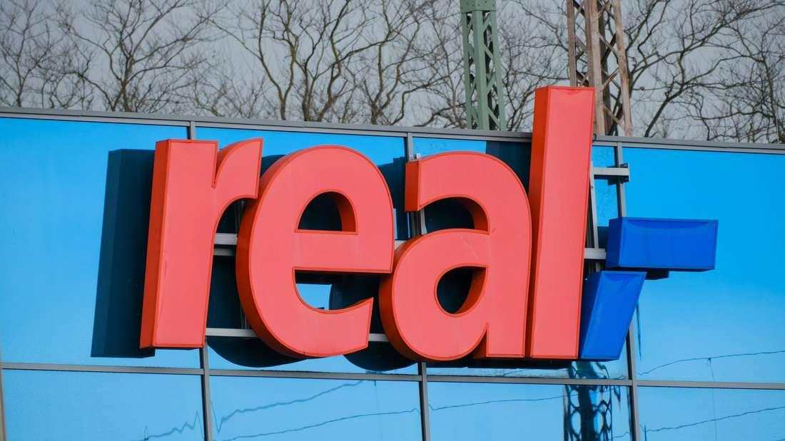Das Logo vom Supermarkt real an einer Filiale.