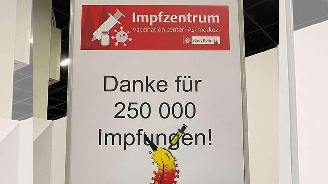 """Ein Schild auf dem """"Danke für 250 000 Impfungen!"""" steht und eine Impfbanane gesprüht wurde."""