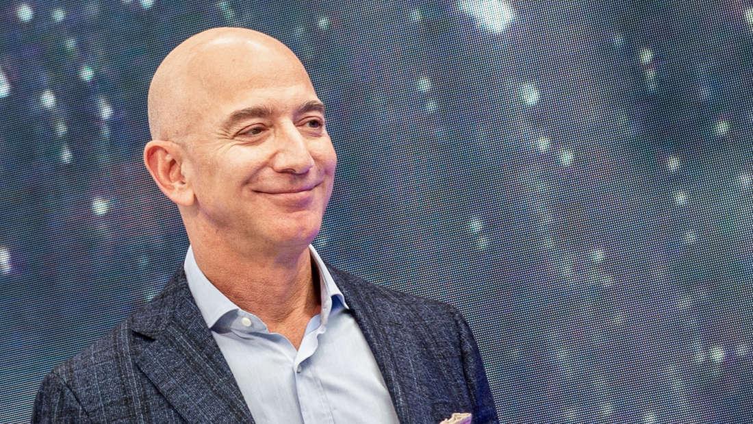 Jeff Bezos lacht und trägt dabei Anzug