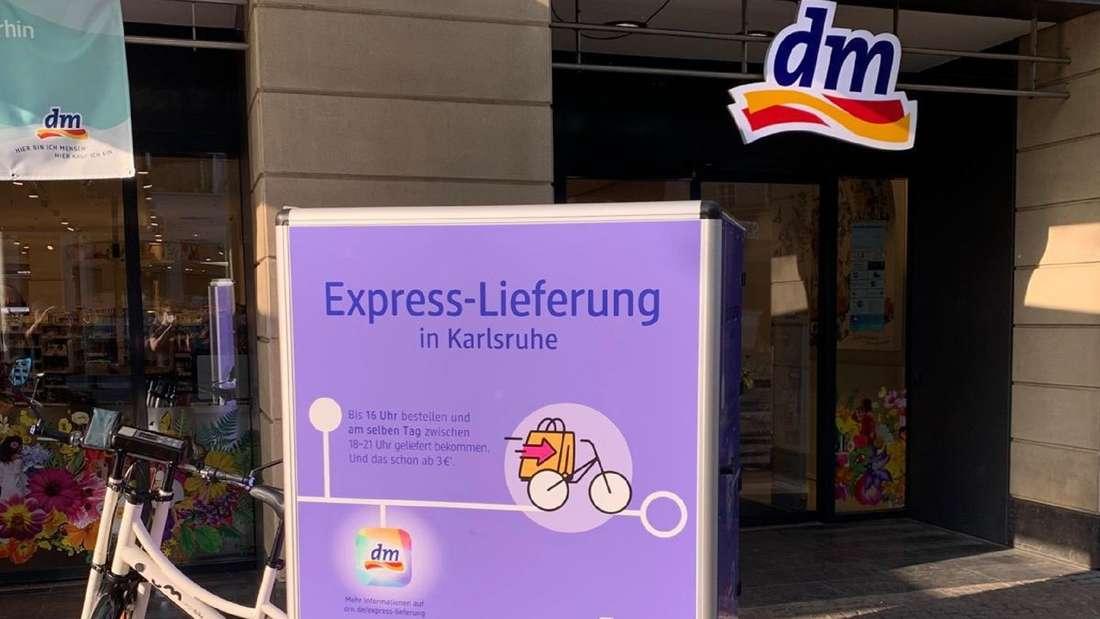 Vor einer dm-Filiale steht ein Lastenrad mit dm-Logo.