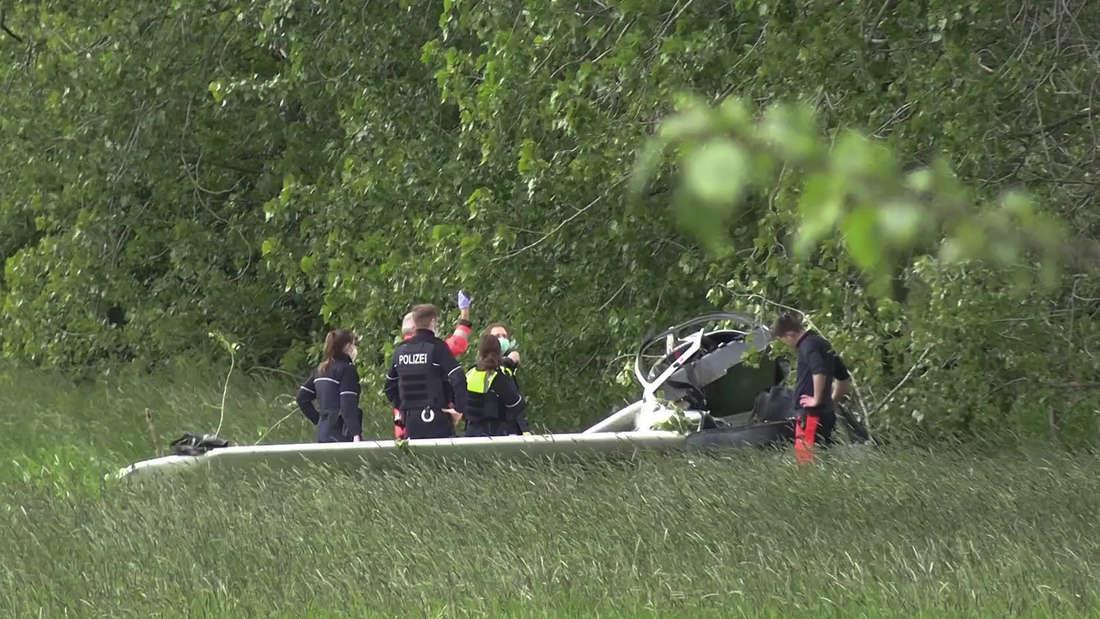 Polizei und Rettungskräfte stehen neben einem abgestürzten Leichtflugzeug.