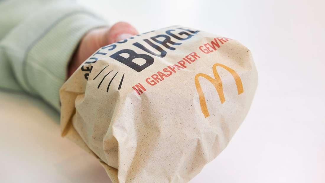 Eine Person hält in einer Hand einen McDonald's-Burger, der in dem gräulichen Graspapier eingepackt ist.