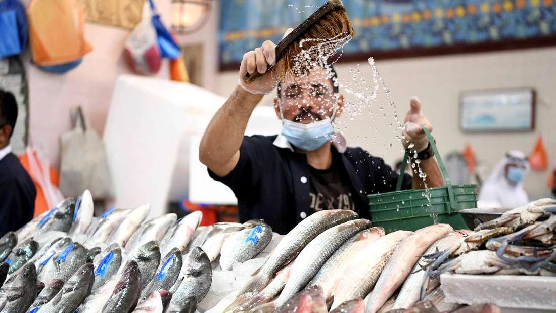 Ein Verkäufer hält auf einem Fischmarkt seine Ware frisch, während er auf Kunden wartet.