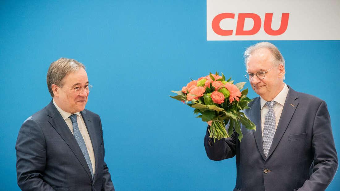 Reiner Haseloff (CDU, r), Ministerpräsident von Sachsen-Anhalt, bekommt einen Blumenstrauß von Armin Laschet.