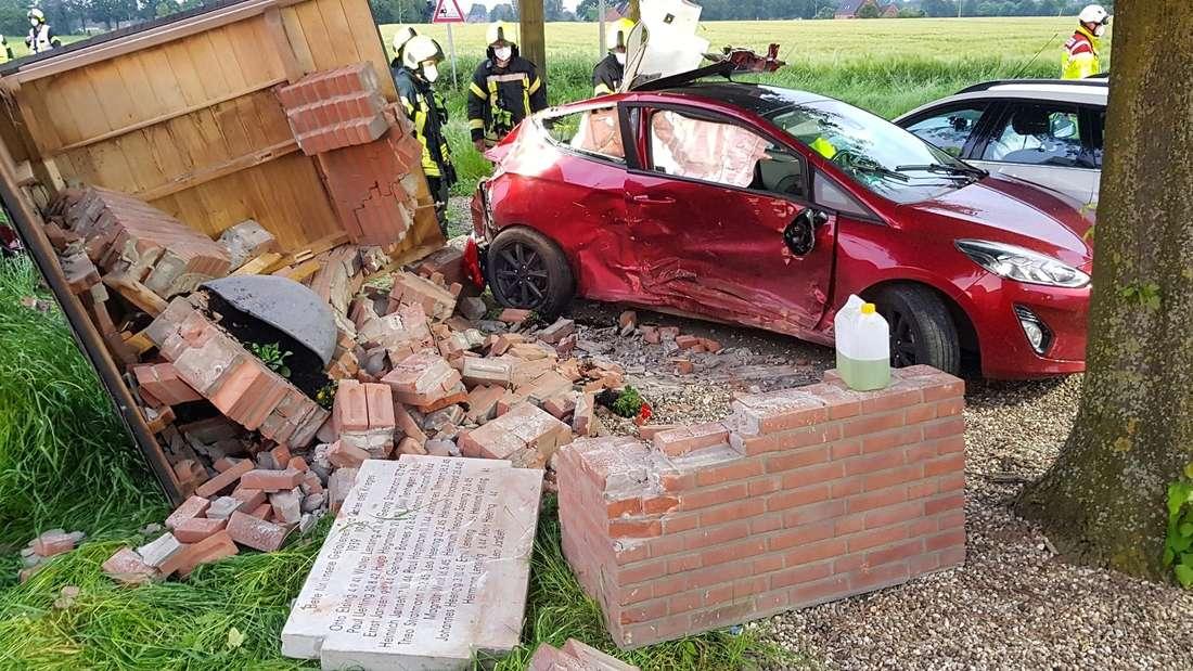 Zwei beschädigte Autos stehen vor einem zerstörten Heiligenhäuschen in Rees (Kreis Kleve).