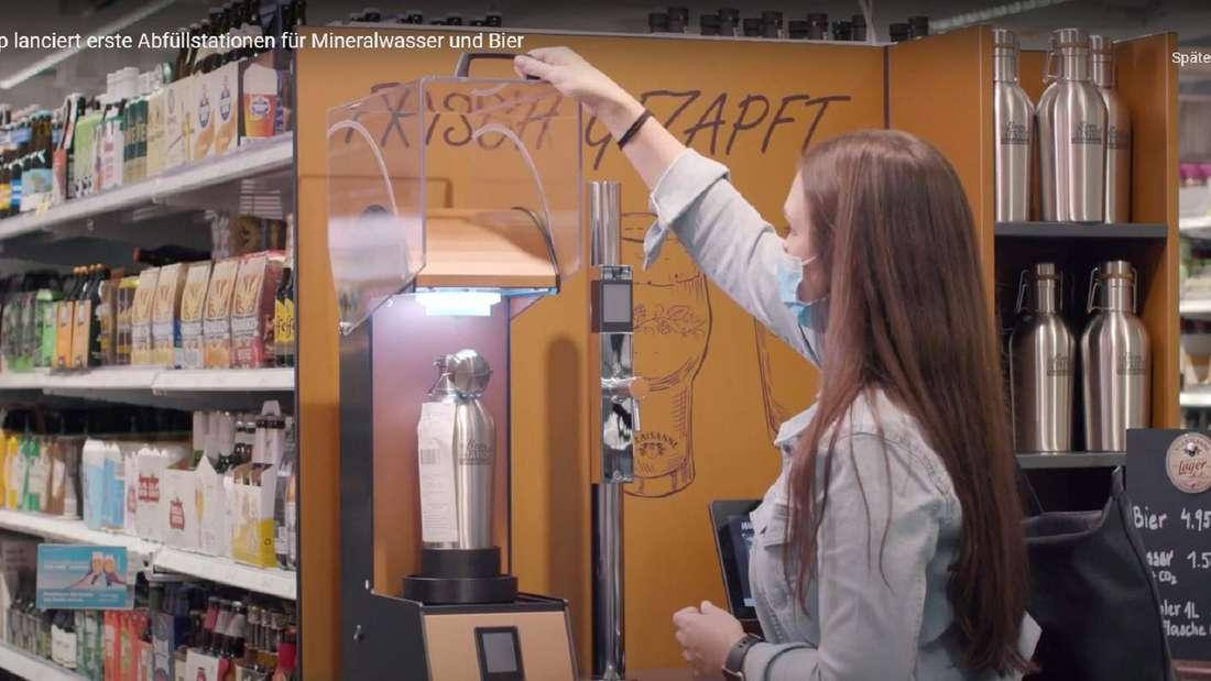 Eine Frau bedient eine Zapfanlage im Supermarkt Coop.