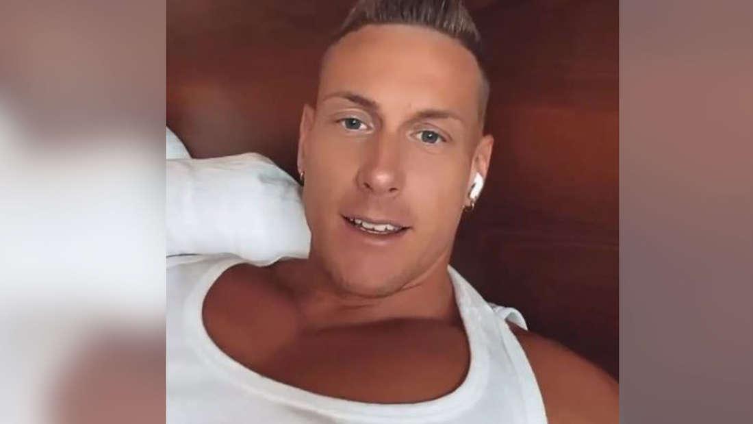 Calvin Kleinen im weißen Unterhemd und Knopf im Ohr