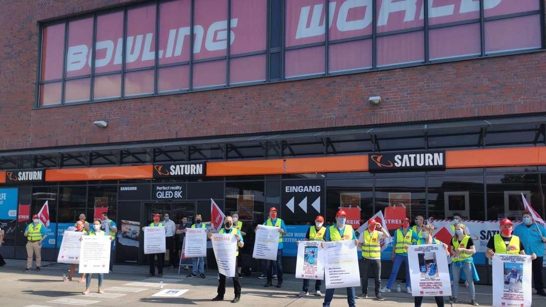 Mitarbeiter stehen in Warnwesten mit Plakaten vor einem Saturn in Düsseldorf-Flingern.
