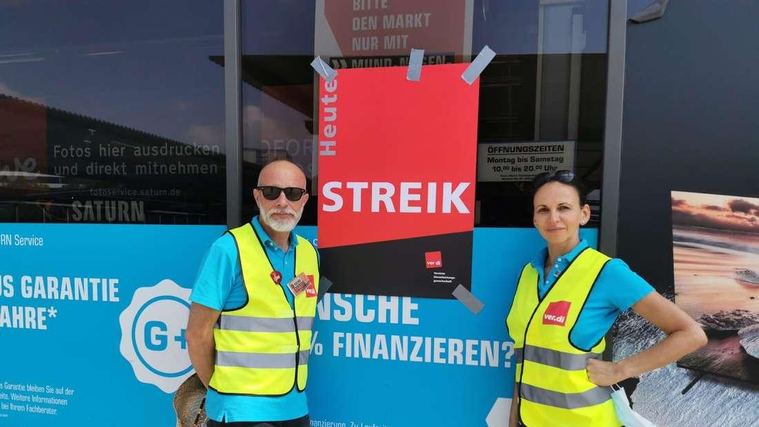 Guido Löffler und Rabia El Jebbari vom Betriebsrat der Saturn-Filiale in Düsseldorf Flingern stehen vor einem Streik-Plakat.