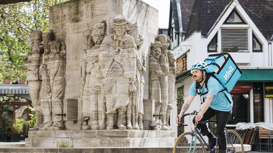 Ein Wolt-Fahrer auf einem Fahrrad durch die Stadt Köln.