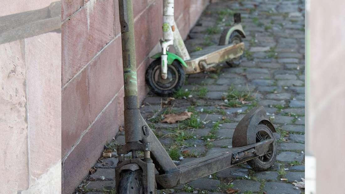 Zwei dreckige E-Scooter stehen an einer Mauer, nachdem sie am Morgen aus dem Wasser geborgen worden waren.