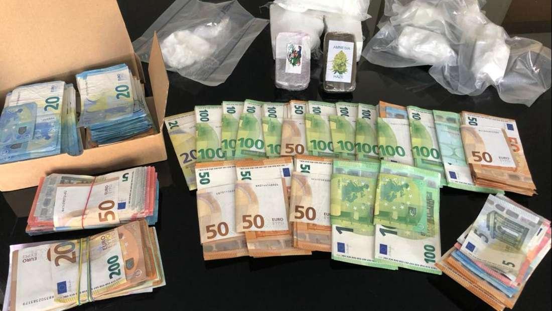 Sichergestelltes Bargeld und Drogen liegen auf einem Tisch im Bonner Polizeipräsidium.