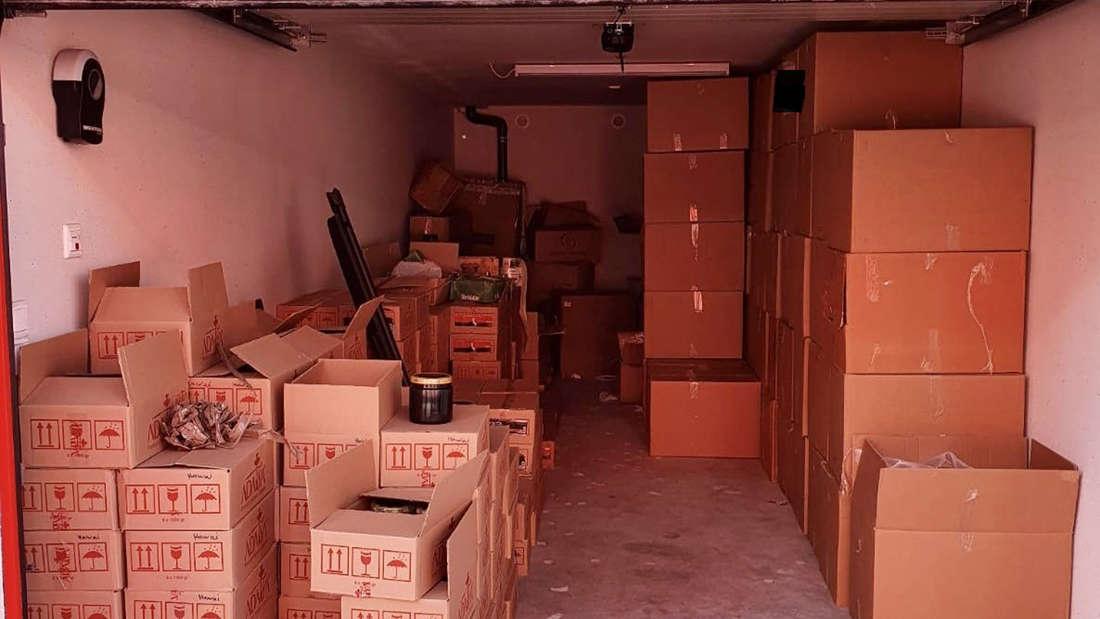Mehrere Pakete mit unversteuertem, gefälschten Wasserpfeifentabak liegen aufeinandergestapelt in Kartons in einem Lager.