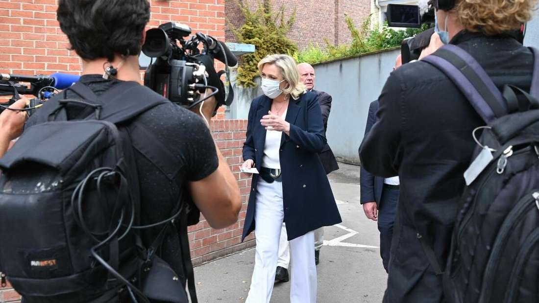 Marine Le Pen, Parteichefin des Rassemblement National, nach der Stimmabgabe für die Regionalwahl in Frankreich, umringt von Kameras.