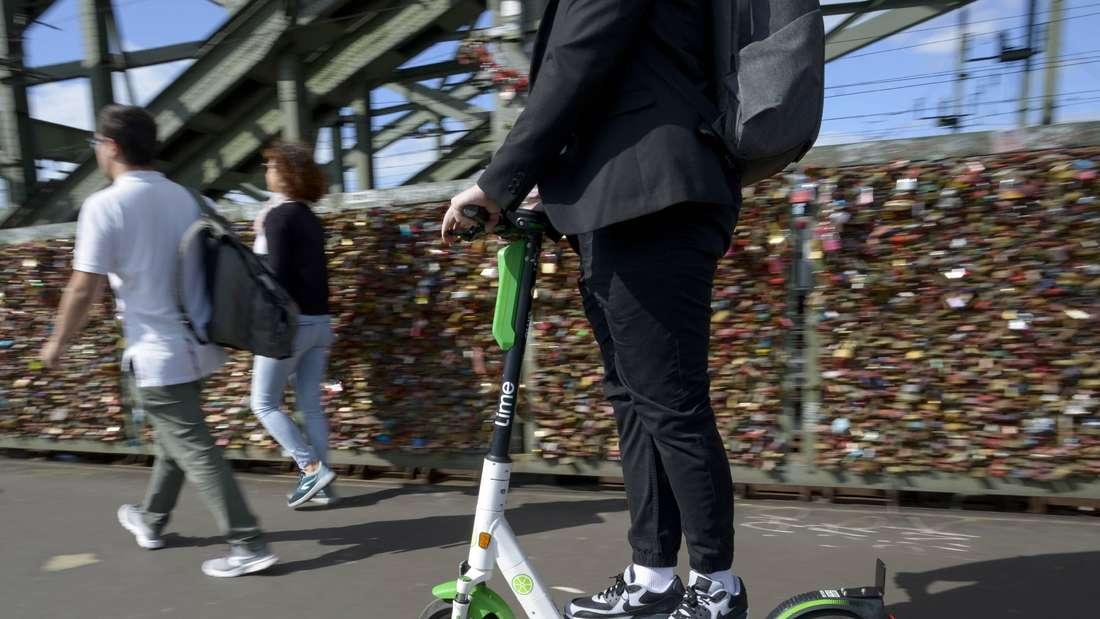 Ein junger Mann fährt mit einem E-Scooter der Verleihfirma Lime auf dem kombinierten Fuss- und Radweg über die Hohenzollernbrücke