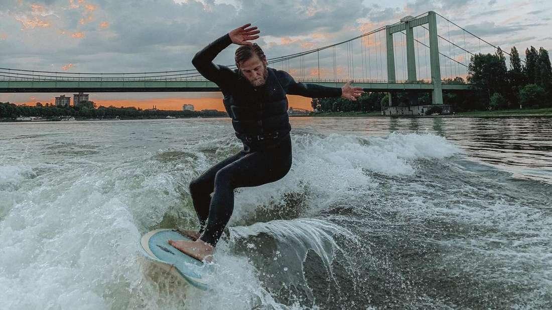 Ein Mann surft auf dem Rhein, im Hintergrund sieht man die Rodenkirchener Brücke.