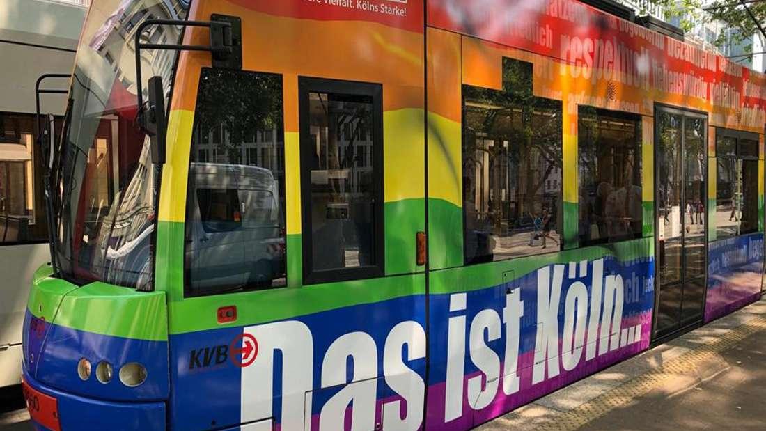 Eine Stadtbahn der KVB in Regenbogenfarben steht an einer Haltestelle.