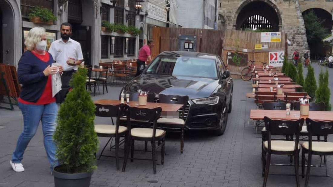 Ein schwarzes Auto steht auf der Fläche einer Außengastronomie.