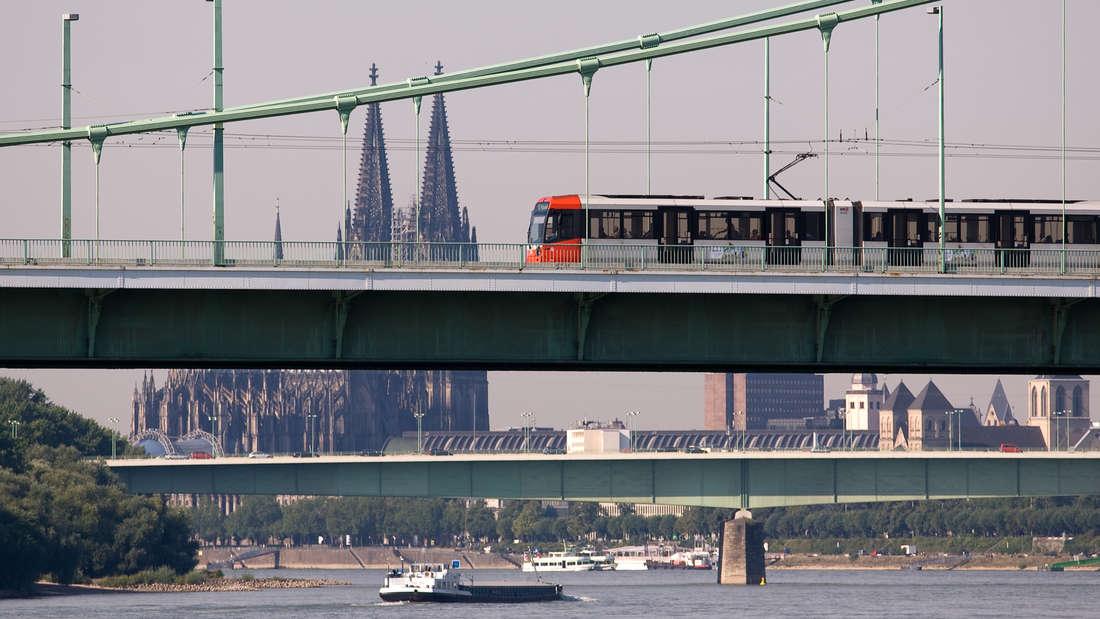 Eine KVB-Bahn fährt über die Mülheimer Brücke. Im Hintergrund ist der Kölner Dom zu sehen.