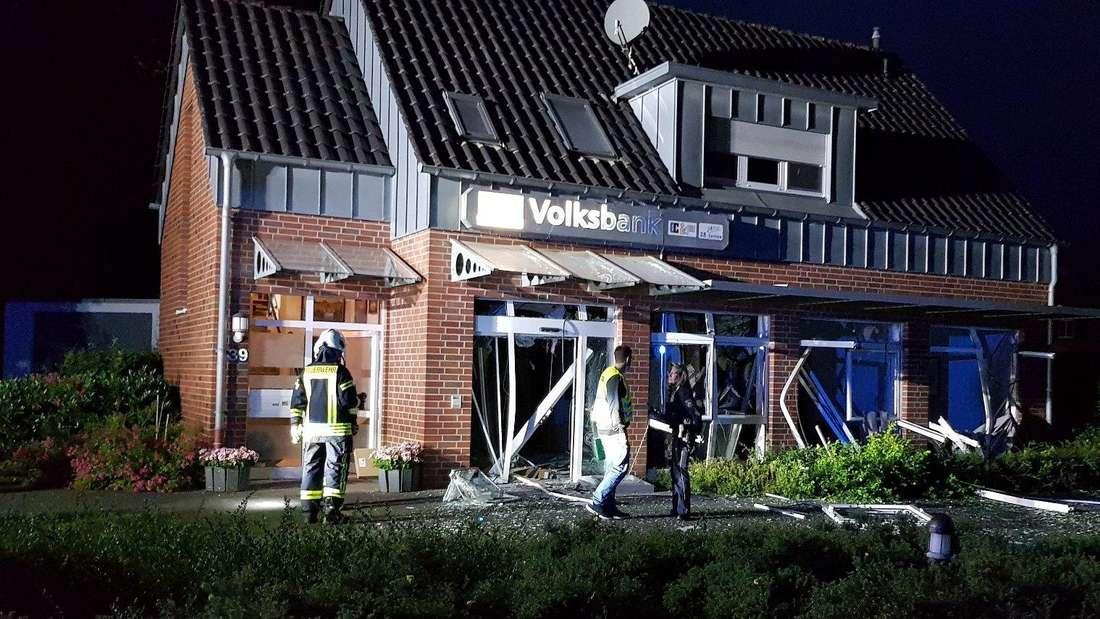 Mitarbeiter von Polizei und Feuerwehr stehen am frühen Morgen vor einer zerstörten Bankfiliale.