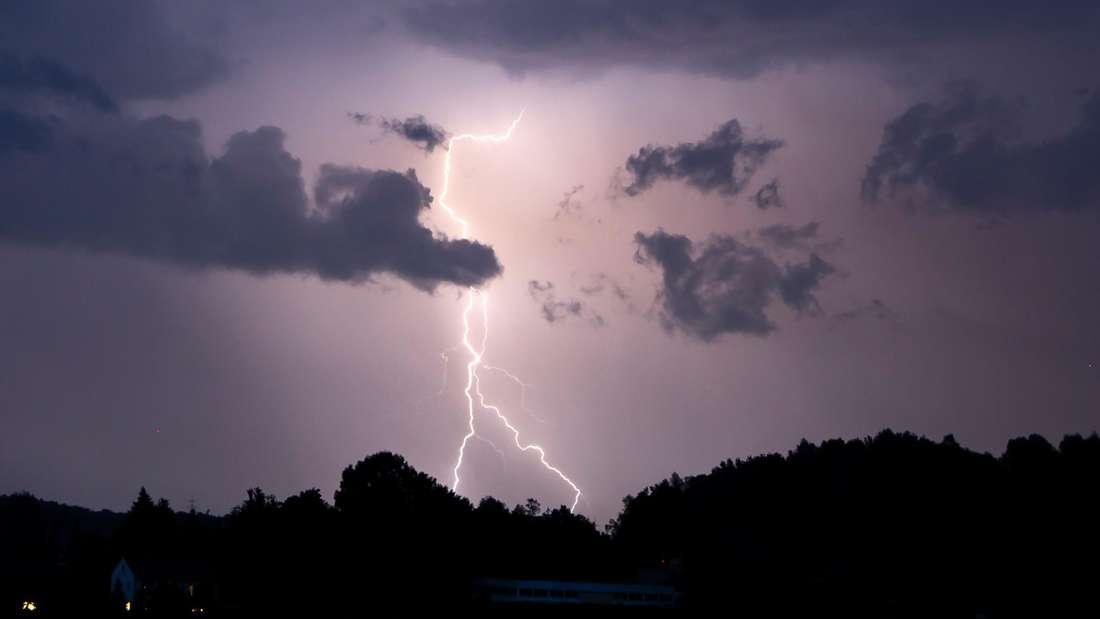 Ein Blitz erhellt den Nachthimmel.