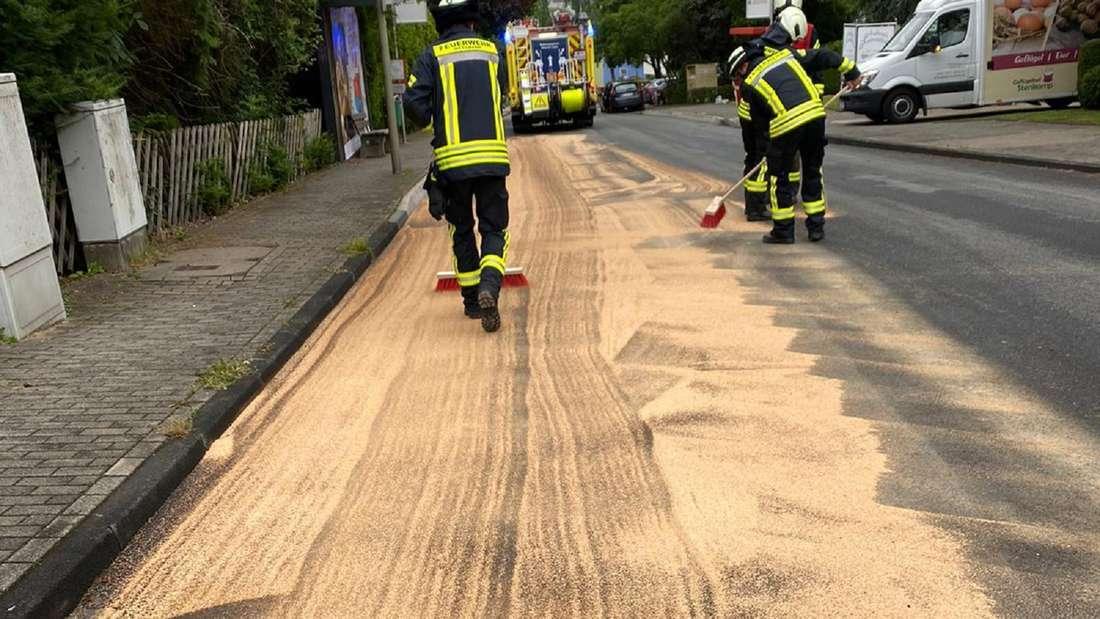 Kräfte der Feuerwehr streuen eine Ölspur ab