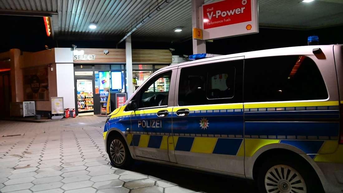 Ein Polizeiauto vor einer Tankstelle.