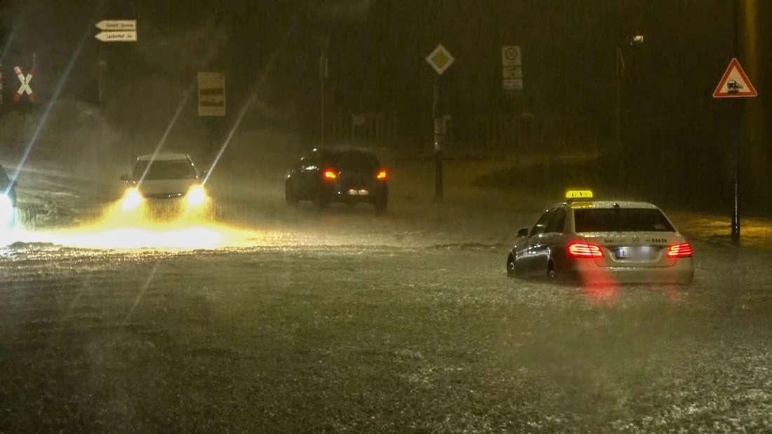 Ein Taxi, das sich im Hochwasser festgefahren hat, steht auf einer überschwemmten Straße.