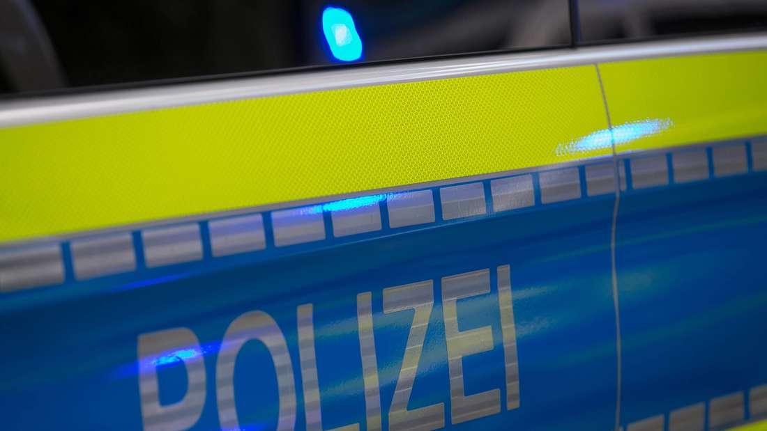 Schriftzug Polizei auf der Tür Seite eines Streifenwagens.