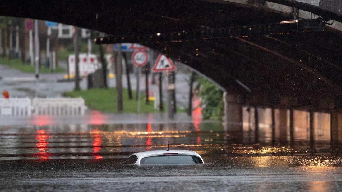 Nur das Dach eines Autos schaut noch aus dem Wasser, das eine Bahnunterführung in Köln geflutet hat.