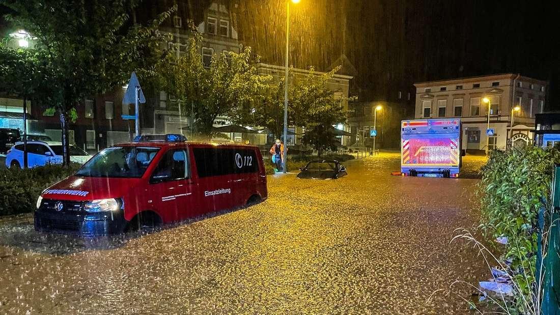 Feuwehrfahrzeuge und ein PKW stehen auf einer überfluteten Straße in Hagen.